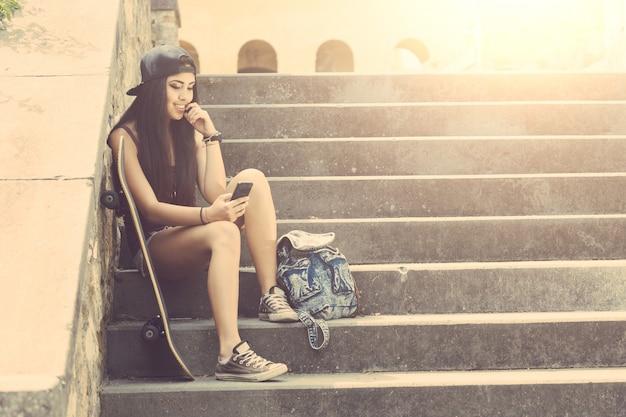 Retrato de una muchacha hermosa del patinador que mira el teléfono elegante