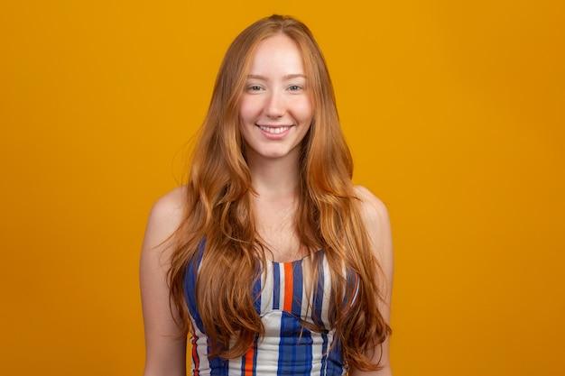 Retrato de muchacha hermosa pelirroja alegre con pelo volando sonriendo riendo sobre pared amarilla.