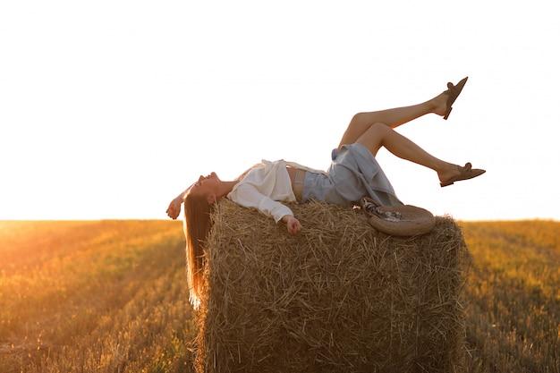 Retrato de la muchacha hermosa en rollo del pajar en campo de trigo cosechado en el verano.
