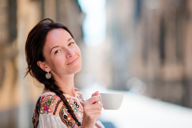 Retrato de muchacha hermosa con taza de café en la calle. turista caucásico disfruta de sus vacaciones europeas en una ciudad vacía