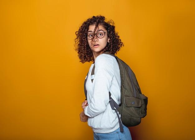 Retrato de una muchacha india sorprendida del estudiante en vidrios con una mochila.