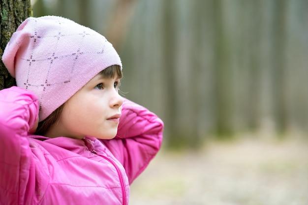 Retrato de la muchacha joven bonita del niño que lleva la chaqueta rosada y el casquillo que se inclinan a un árbol en bosque que disfruta de día soleado cálido a principios de primavera al aire libre