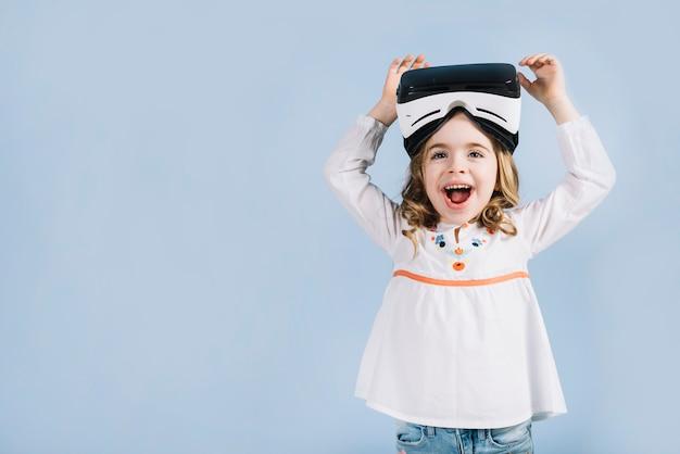 Retrato de una muchacha linda emocionada con auriculares de realidad virtual contra el fondo azul