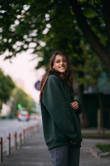 El retrato de la muchacha linda con el pelo largo mira la cámara en ciudad en fondo de la calle.