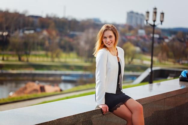 Retrato de la muchacha linda que sonríe a la cámara en ciudad en fondo bulding en día soleado.