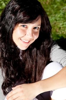 Retrato de la muchacha morena hermosa con los ojos azules en hierba verde en el parque.