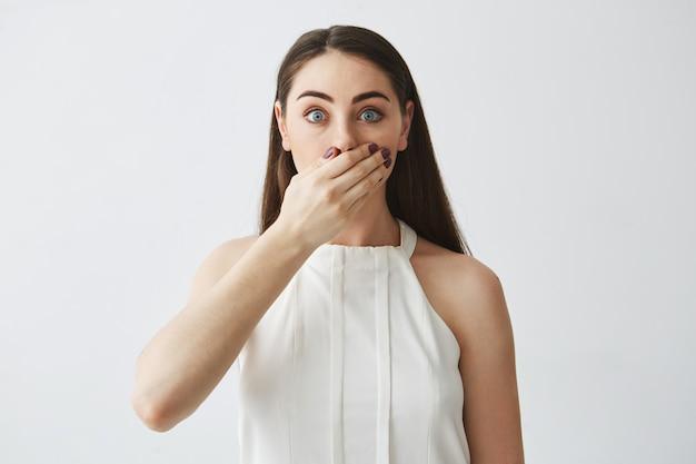 Retrato de la muchacha morena joven sorprendida que cubre la boca con la mano.