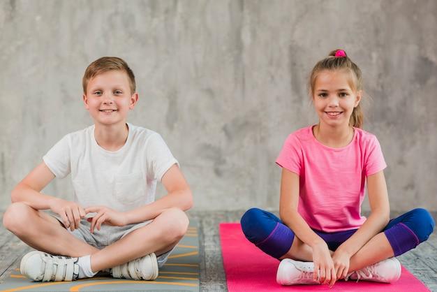 Retrato de una muchacha y un muchacho sonrientes que se sientan en la estera del ejercicio con sus piernas cruzadas delante de la pared