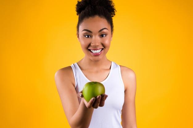 Retrato de la muchacha negra con la manzana verde aislada.