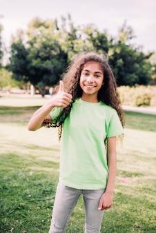 Retrato de una muchacha con los pelos rizados que muestran el pulgar que se levanta en parque
