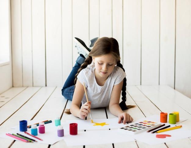 Retrato de una muchacha que miente en el suelo de madera que pinta la estrella amarilla con la brocha