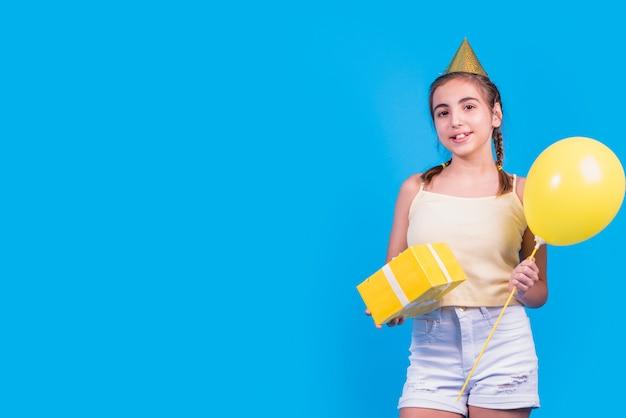 Retrato de una muchacha que sostiene la caja y los globos de regalo en su mano en superficie azul