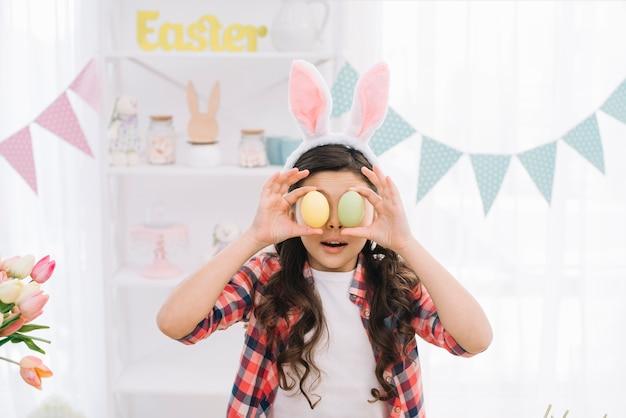 Retrato de una muchacha que sostiene los huevos de pascua delante de sus ojos el día de pascua en casa