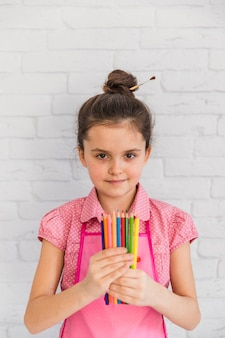 Retrato de una muchacha que sostiene los lápices multicolores en la mano que se opone a la pared de ladrillo blanca