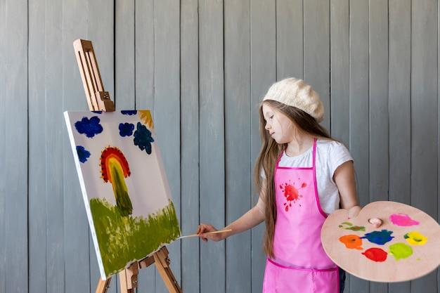 Retrato de una muchacha que sostiene la paleta de madera en la pintura de la mano en la base con el cepillo