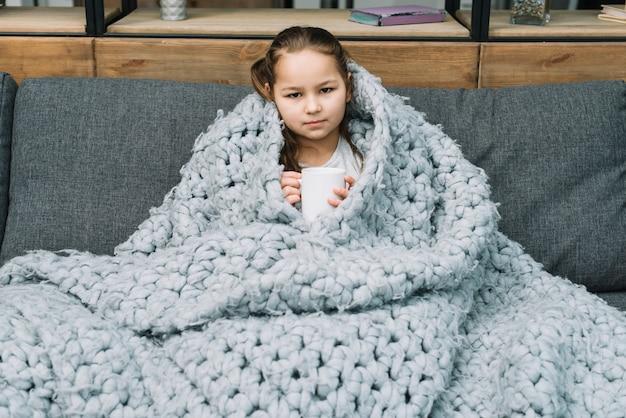 Retrato de una muchacha que sostiene la taza de café que se sienta en el sofá con la bufanda cubierta