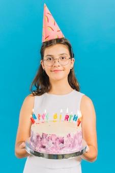 Retrato de una muchacha que sostiene la torta de cumpleaños en fondo azul