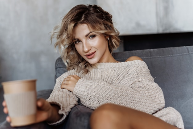 Retrato de la muchacha rubia moderna atractiva joven que se sienta en un sofá que sostiene un vidrio de café