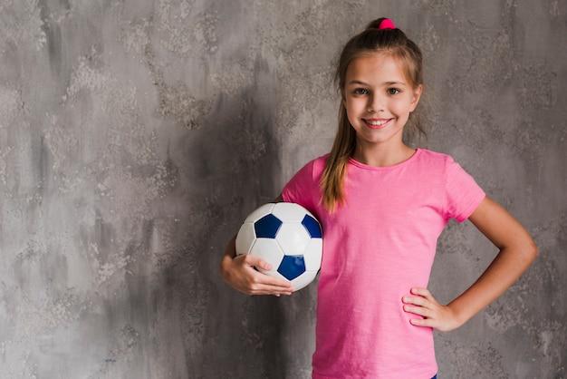 Retrato de una muchacha rubia sonriente con la mano en la cadera que sostiene el balón de fútbol contra la pared gris
