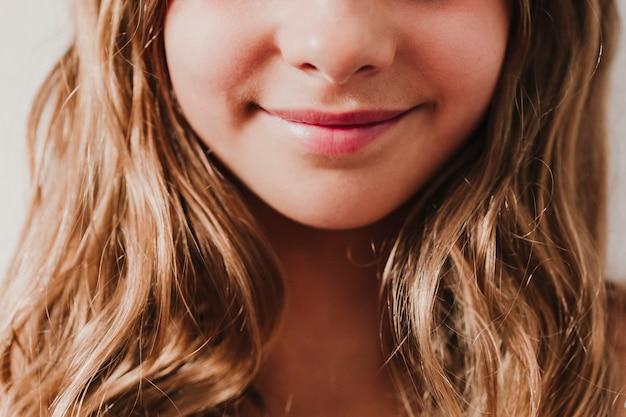 Retrato de muchacha sonriente adolescente irreconocible en casa. fondo blanco, vista cercana. concepto de felicidad y estilo de vida.