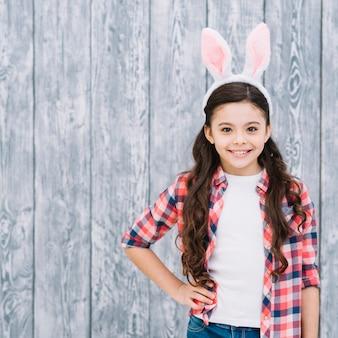 Retrato de una muchacha sonriente confiada con el oído del conejito en la cabeza contra el contexto de madera