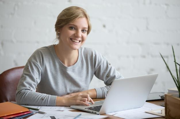 Retrato de una muchacha sonriente del estudiante en el escritorio con la computadora portátil