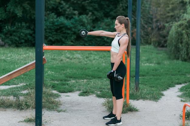 Retrato de la muchacha sonriente hermosa con pesas de gimnasia, entrenamiento al aire libre en parque.