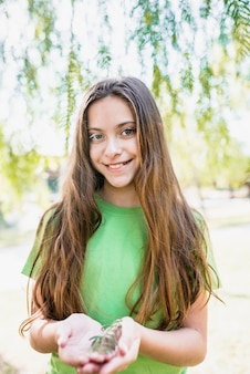 Retrato de una muchacha sonriente con el pelo largo que sostiene la ramita en las manos que miran la cámara