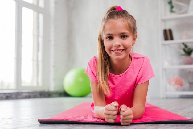 Retrato de una muchacha sonriente que ejercita en la estera rosada