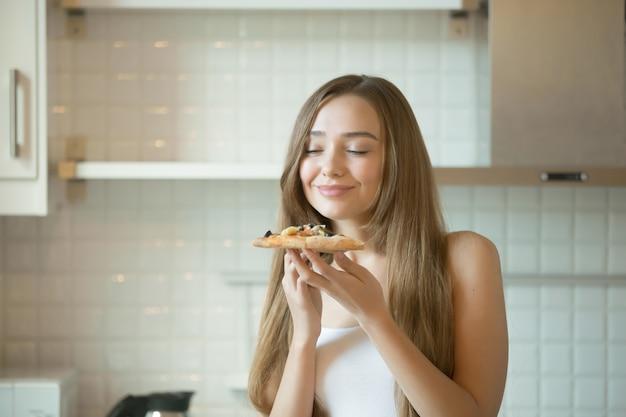 Retrato de una muchacha sonriente que inhala el aroma de la pizza