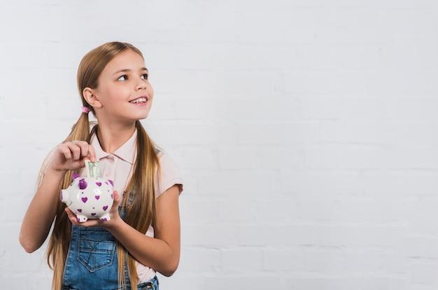 Retrato de una muchacha sonriente que inserta la nota de la moneda en el piggybank blanco que mira lejos