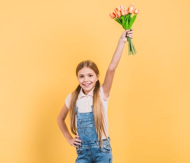 Retrato de una muchacha sonriente que levanta su mano que sostiene tulipanes en la mano que se opone al contexto amarillo