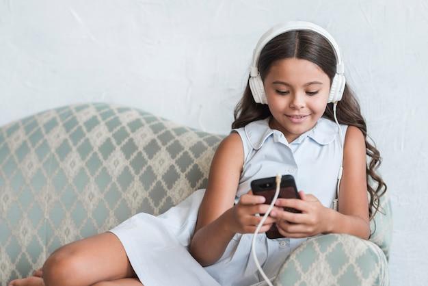 Retrato de una muchacha sonriente que se sienta en el sofá usando el teléfono móvil con los auriculares en su cabeza