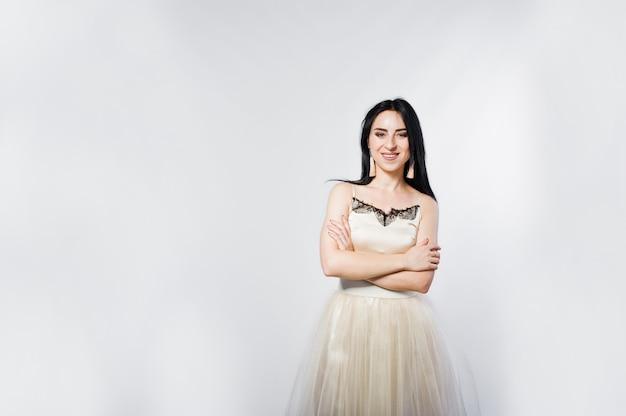 Retrato de la muchacha triguena en el vestido beige aislado en blanco.