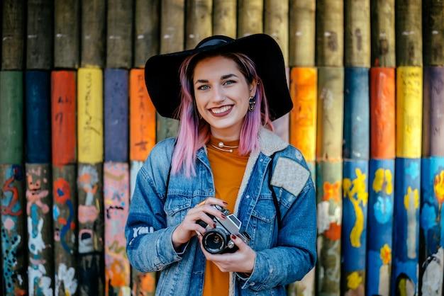 Retrato de una muchacha turística con el pelo teñido y un sombrero que se coloca delante de una pared pintada.