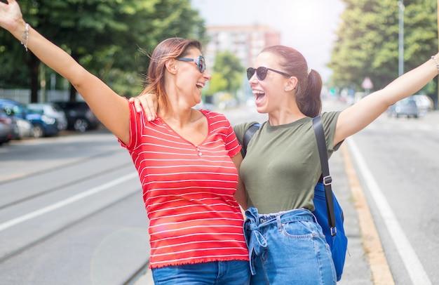El retrato de muchachas sonrientes hermosas jovenes en una pizca del día de verano coloreó la ropa y los vaqueros de la camiseta
