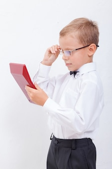Retrato de muchacho adolescente con calculadora sobre fondo blanco.