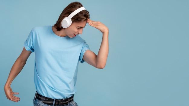 Retrato de muchacho adolescente fresco escuchando música