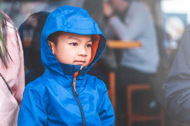 Retrato del muchacho asiático del niño en la ropa azul del invierno