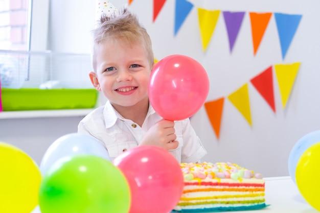 Retrato del muchacho caucásico rubio que sonríe en la cámara cerca de la torta de cumpleaños del arco iris. fondo colorido festivo con globos