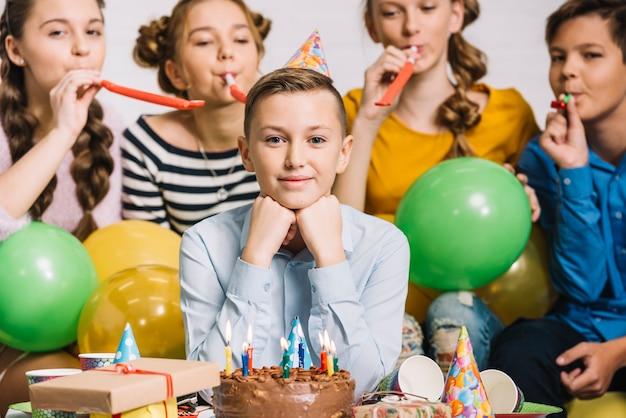 Retrato de un muchacho del cumpleaños con sus amigos que soplan el cuerno del partido