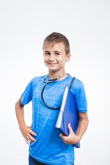 Retrato de un muchacho feliz que sostiene la carpeta en el fondo blanco