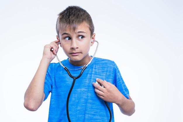Retrato de un muchacho que controla su latido del corazón con el estetoscopio en el fondo blanco