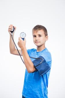 Retrato de un muchacho que mide la presión arterial en el fondo blanco