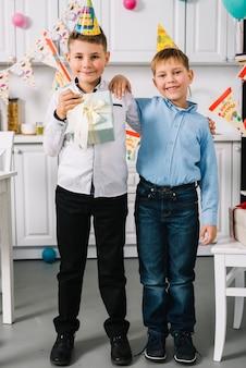 Retrato de un muchacho sonriente del cumpleaños que se coloca con su amigo en la cocina