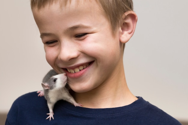 Retrato del muchacho sonriente lindo divertido feliz hermoso del niño con el hámster blanco del ratón del animal doméstico en hombro en luz. mantener mascotas en casa, cuidar y amar a los animales.