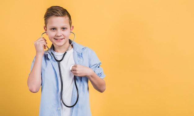 Retrato de un muchacho sonriente que controla su latido del corazón con el estetoscopio contra fondo amarillo