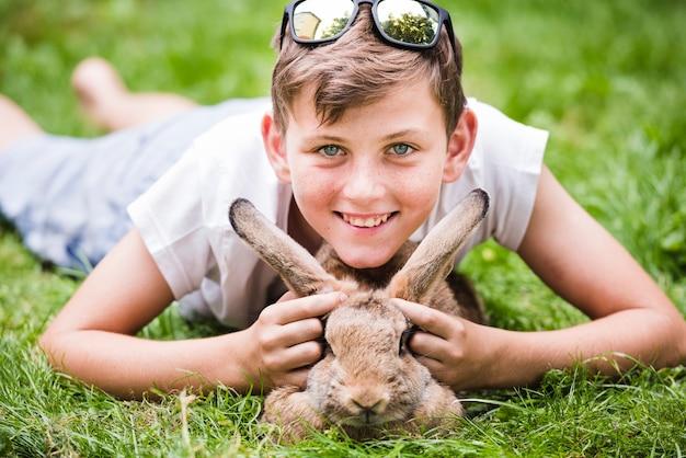 Retrato del muchacho sonriente que miente sobre conejo en hierba verde en el parque