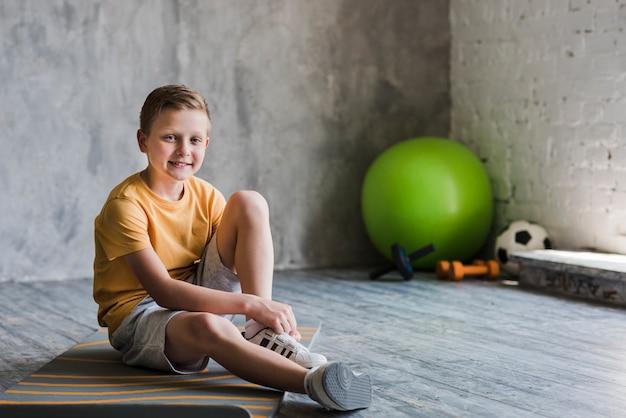 Retrato de un muchacho sonriente que se sienta en la estera del ejercicio que mira la cámara