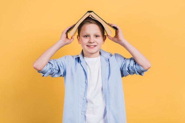 Retrato de un muchacho sonriente que sostiene el libro sobre su cabeza que mira a la cámara contra fondo amarillo
